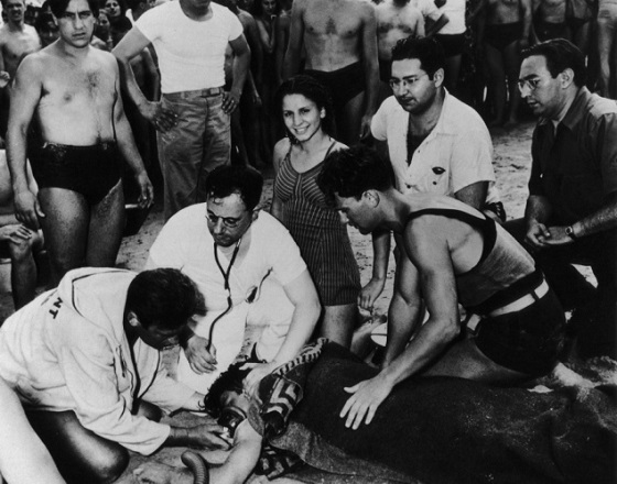 Girl smiling beside lifeless body of drowned boyfriend at Coney Island, 1940
