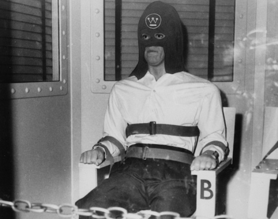 Prisoner in gas chamber moments before death. Incongruously, his black hood bears the logo of Westinghouse Electric