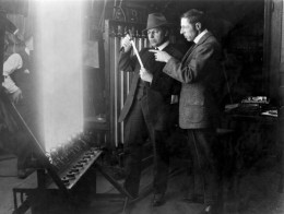 Cameraman Billy Bitzer (L.) and D. W. Griffith experiment with lighting techniques, 1913