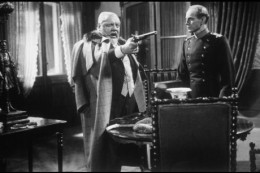 The Colonel wields his dueling pistol, while a concerned Max looks on